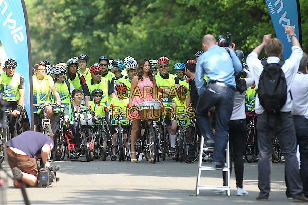 Kelly Brook on a Sky Ride promotion in Regents Park, London, England..May 29th, 2012.full length pink white print sleeveless dress bike bicycle photographers press ladder .CAP/HIL.©John Hillcoat/Capital Pictures .