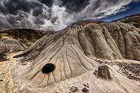 A lone stone embedded in an eroded matrix of bentonite in the Lybrook Badlands of northwestern New Mexico with dramatic clouds in the sky.