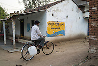 A customer cycles to the iJal water station to buy drinking water in Gorikathapalli, a remote village in Warangal, Telangana, India, on 22nd March 2015. Safe Water Network works with local communities that live beyond the water pipeline to establish sustainable and reliable water treatment stations within their villages to provide potable and safe water to the communities at a nominal cost. Photo by Suzanne Lee/Panos Pictures for Safe Water Network