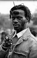 """milano, manifestazione euro mayday parade 2007. """"qual'è la tua condizione economica/lavorativa?""""  THUNDER, 29 anni, dj. """"Vengo dal Gambia, lo stato più piccolo dell'Africa. Naturalmente non riesco a vivere facendo.solo il dj ma lavoro anche per delle cooperative. Amo la musica e sogno un giorno di tornare a casa per aprire un'attività vicino al mare dove vivono i miei. In Italia non si sa, ma il Gambia e' un paese turistico con delle spiagge lunghissime e tante situazioni dove si ascolta la musica raggae. Gli stessi giamaicani vengono li' volentieri per fare dei concerti....."""" --- milan, euro mayday parade 2007 demonstration. """"How is your economic and working condition?""""  THUNDER, 29, dj. """"I come from Gambia, the smallest state in africa. Of course I can't live only of playing disc-jockey but I do also work for some cooperatives. I love music and I dream of returning back home one day and start up a business near the sea where my parents live. In italy people don't know but Gambia is a tourist country with very long beaches and many situations where one listens to reggae music. Even Jamaican love to go there and play some concerts..."""""""