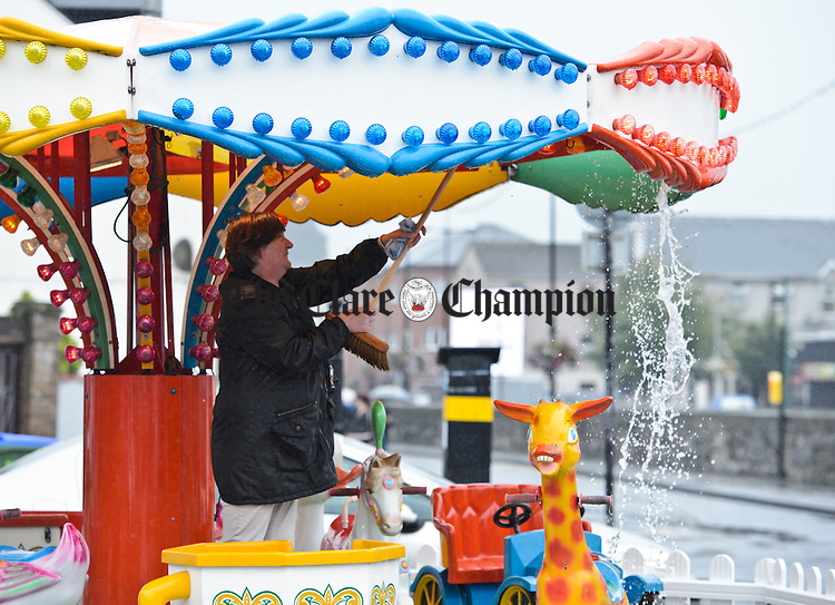 Street trader Ursula Harford removes the water from the top of her carousel during Fleadh Cheoil na hEireann in Ennis. Photograph by John Kelly.