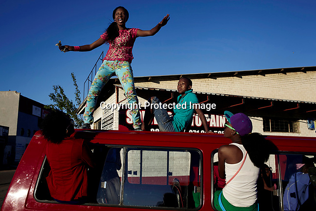 SOWETO, SOUTH AFRICA SEPTEMBER 29: Izikhothane youth dance and display their clothes and cash on September 29, 2012 in Thokoza Park, Soweto, South Africa. Hundreds of Izikhothane kids gathered in Thokoza Park and moved on to other areas in Soweto, to show off their dance moves and play loud music. The Izikhothane bling kids are the new fears of residents and parents in the townships of Johannesburg. They buy (and sometimes burn and destroy) fancy brand clothes and shoes in Soweto. They also like to drink and display expensive bottles of alcohol. Many of these kids are desperate to get the latest clothes and the pressure is hard on their parents. (Photo by: Per-Anders Pettersson)