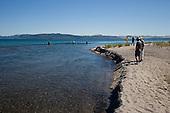 Trout fishermen fishing the Waitahunui river mouth, with tourists watching, Lake Taupo, Waikato, New Zealand