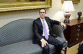 United States Secretary of the Treasury Steve Mnuchin sits on a couch in the Roosevelt Room of the White House in Washington, DC prior to a meeting with US President Donald J. Trump to discuss the Federal budget on February 22, 2017 in Washington, DC. <br /> Credit: Olivier Douliery / Pool via CNP