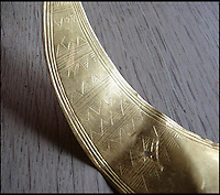 BNPS.co.uk (01202 558833)<br /> Pic: RogerGuttridge/BNPS<br /> <br /> Design etched into the solid gold torc.<br /> <br /> 3500 year old solid gold torc found in a Dorset field.<br /> <br /> A peckish metal detectorist struck gold after leaving his machine on by accident as he went off for his lunchtime sandwich.<br /> <br /> David Spohr had given up after a fruitless morning searching the Tarrant Valley in Dorset and was walking to get his sandwiches when his metal detector went off.<br /> <br /> Curious to know what had triggered the detector he started digging and soon spotted a dull metal object which at first he thought was a rusty old sardine tin.<br /> <br /> But as he dug deeper he realised it was more than it first appeared - and after wiping the mud off it up he was shocked to find it was made from solid gold.<br /> <br /> Amazingly, the unremarkable lump was revealed to be a gold lunula, a crescent-shaped necklace dating back to the Bronze Age.<br /> <br /> Lunulas were worn by ancient tribal leaders as a symbol of power and authority.<br /> <br /> The lunula David found, which weighs 71.5 grams, is one of only a handful dug up in mainland Britain and is thought to be the first discovered using a metal detector.