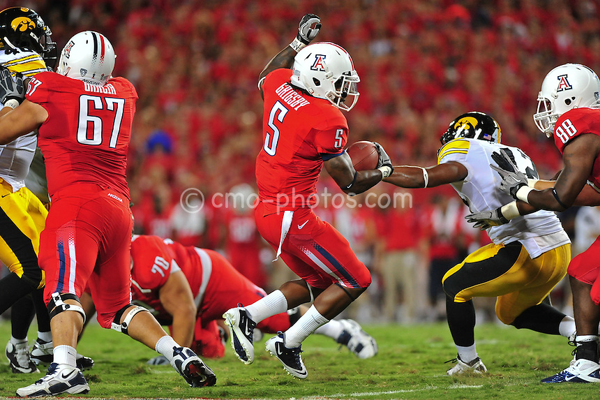 Sept 18, 2010; Tucson, AZ, USA; Arizona Wildcats running back Nic Grigsby (5) avoids a tackle in the 1st quarter of a game against the Iowa Hawkeyes at Arizona Stadium. Grigsby would later lose a fumble on this run.