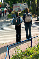Two girls waiting to cross the street in Poland.  Rawa Mazowiecka  Central Poland