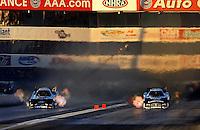 Nov 13, 2010; Pomona, CA, USA; NHRA funny car driver John Force (left) races alongside Matt Hagan during qualifying for the Auto Club Finals at Auto Club Raceway at Pomona. Mandatory Credit: Mark J. Rebilas-