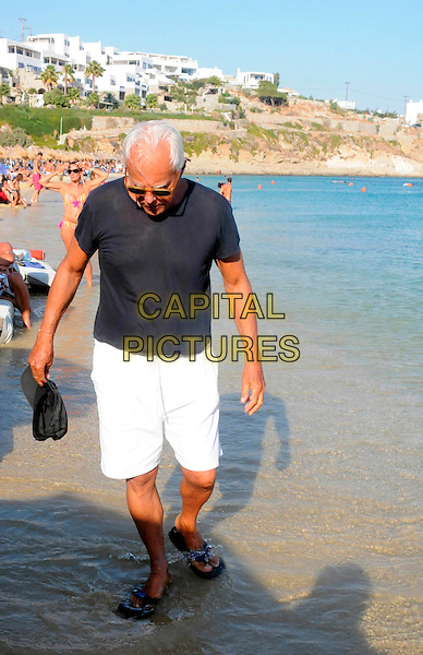 GIORGIO ARMANI .Spotted on Psarou Beach, Mykonos Island, Greece..August 18th, 2008.full length sunglasses shades black t-shirt white shorts water baseball cap hat  water flip flops.CAP/PPG.© Tarsos/People Picture/Capital Pictures