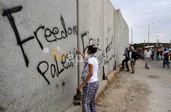 A Palestinian protester sprays a slogan reading in Arabic 'Free Prisoners' on a concrete segment of a separation wall in the West Bank city of Tulkarem, 31 May 2014. Reportedly dozens of Palestinians were injured during clashes with Israeli forces that erupted after protesters tried to damage and remove parts of the Israeli separation wall during a march to support Palestinian prisoners in Israeli jails. Photo by Nedal Eshtayah