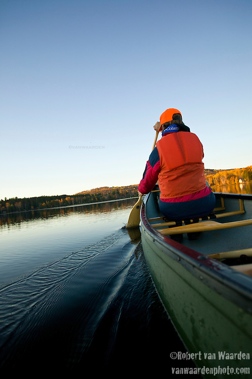 A boy in an orange life jacket and cap paddles a canoe on a lake while the autumn leaves turn color near Barry's Bay, Ontario, Canada.