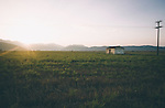 Sunset over a pastoral rural scene in Greece with mountains and a farm building