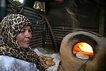 Palestinian woman bakes a loaves in mud oven in Gaza City, due to power outages and Israeli restrictions on supply gaza by fuel. The top United Nations human rights official today called on Israel to immediately lift its blockade of the Gaza Strip which she said violates international law.