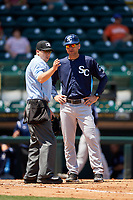 Charlotte Stone Crabs manager Michael Johns (9) talks with an umpire during a game against the Bradenton Marauders on April 9, 2017 at LECOM Park in Bradenton, Florida.  Bradenton defeated Charlotte 5-0.  (Mike Janes/Four Seam Images)