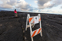 A woman hikes over the old lava fields of (Hawai'i) Volcanoes National Park to see the lava flow, Hawai'i Island. A sign directing visitors to the lava flow is in the foreground.