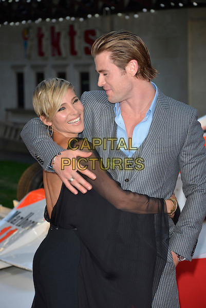 Elsa Pataky and Chris Hemsworth<br /> 'Rush' world film premiere at the Odeon Leicester Square cinema, London, England.<br /> 2nd September 2013<br /> half length suit grey gray black  sheer married husband wife  jumpsuit waistcoat  backless arm around shoulder looking over shoulder smiling profile <br /> CAP/PL<br /> &not;&copy;Phil Loftus/Capital Pictures