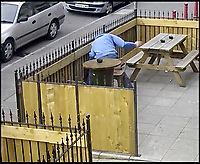 BNPS.co.uk (01202 558833)<br />Pic:   BuffaloBar/BNPS<br /> <br /> CCTV still image of the thug punching the dog.<br /> <br /> The shocking moment a thug rams his pet dog head-first into a fence and repeatedly punches it has been caught on CCTV.<br /> <br /> The yob owner became angry that the black pitbull-type dog ran off into the front garden of a bar.<br /> <br /> After catching up with the animal, the man grabbed it by the neck and slammed it into the wooden fence.