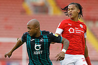 (L-R) Andre Ayew of Swansea City challenged by Toby Sibbick of Barnsley during the Sky Bet Championship match between Barnsley and Swansea City at Oakwell Stadium, Barnsley, England, UK. Saturday 19 October 2019