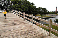 A young boy runs over a bridge leading to Currituck Lighthouse in Corolla, N.C. The Currituck Beach Lighthouse, an Outer Banks lighthouse, is one of the few North Carolina lighthouses today that allow visitors to climb to the top. .