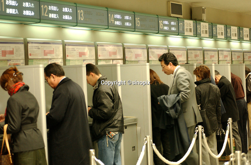 People with draw cash from ATM's at the Fuji Bank in  Shinjuku district of Tokyo. Japan's banking system faces a crunch period in the months ahead due to the shrinking economy and biting recession.....