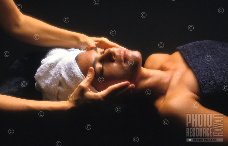 A woman receives a massage and facial at an island health spa.
