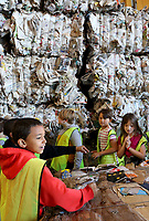 NWA Democrat-Gazette/DAVID GOTTSCHALK Cory Benjamin (left), a second grade student in Chad Lechtenberger's class at Washington Elementary School, looks Monday, May 13, 2019, at recycled newspaper and cardboard during a tour of the Material Recovery Facility in Fayetteville. The students toured the city of Fayetteville Transfer Station as part of unit studying natural resources and recycling environmental issues.