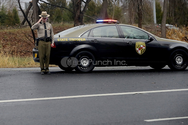 A Maryland State Trooper salutes as United States President Donald J. Trump's motorcade heads to Walter Reed National Military Medical Center for his annual physical examination January 12, 2018 in Bethesda, Maryland. Trump will next travel to Florida to spend the Dr. Martin Luther King Jr. Day holiday weekend at his Mar-a-Lago resort. <br /> Credit: Chip Somodevilla / Pool via CNP /MediaPunch