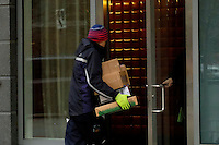 A Fedex worker delivers packages to customer in the Manhattan borough of New York. 12/26/2015. FedEx drivers work overtime to deliver packages to customers furious over late Christmas deliveries. photo by VIEWpress