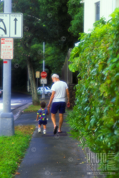 Grandfather and grandson take a rainy day walk in Manoa Valley, Oahu