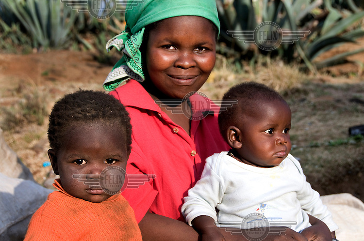Malimpho Thato with her two children, left, 2 year old Reitumetse and right, 6 month old Pontso, in the village of Ha Tsola...