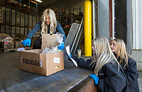 Michelle Thompson (from left) of Bentonville, daughter Brooklyn Thompson, 14, and friend Lily Grace Hassebrock, 13, of Springdale double check the items in an order Saturday, March 21, 2020, at Kimball and Thompson Produce in Lowell. The business supplies fresh produce to the food service industry, including public schools, restaurants and hotels. With many of their usual clients closed due to the covid-19 pandemic, owner Chris Thompson says they are adapting to get their inventory directly to consumers who need it at wholesale prices. Thompson says he is also reaching out to the Northwest Arkansas Food Bank to make sure nothing goes to waste. <br /> <br /> The business began selling to the public Friday morning, and many shelves were already bare Saturday. Thompson says they will be working to keep their inventory updated as they navigate the temporary change to their business model. <br /> <br /> Staff and family members are pitching in to help fill orders curbside while minimizing personal contact and practicing strict sanitizing measures. Customers are asked to place orders ahead of time by calling 479-872-0200 or emailing orders@ktproduce.com. Pickup times are Monday through Saturday from 9 a.m. to 4 p.m., and Sunday from 11 a.m. to 2 p.m. at 305 S. Lincoln St. in Lowell. <br /> <br /> Check out nwaonline.com/200322Daily/ for today's photo gallery.<br /> (NWA Democrat-Gazette/Ben Goff)