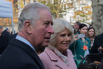Prince Charles and Camilla the Duchess of Cornwall at the Swiss Cottage farmers market, meeting stall holders. Charles relaxed and laughing, Camilla with a cake cutter. Body guards are standing behind them. Its is the 20th anniversary of London Farmers Market.   UK 2019. 2010s