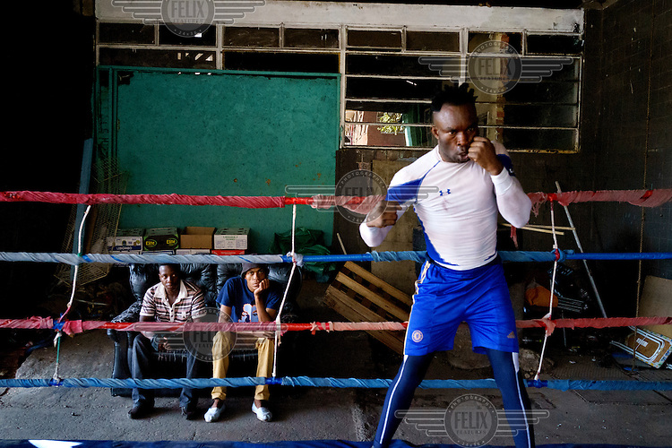 Nigerian-Liberian boxer, Angel Harrison, shadow boxing as gym patrons look on at the Hillbrow Boxing Club. Harrison says he came to South Africa to turn professional, and hopes to qualify for his boxing license. After gunshot injuries put an end to his own boxing career, George Khosi founded the club to instil discipline, camaraderie and an activity away from the streets for young people from the community, and also to provide a training space for upcoming professional boxers. The club operates in a donated space on the forecourt of a disused petrol station in Hillbrow, one of the country's most notorious neighbourhoods.