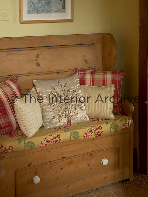 A rustic pine bench is piled with a collection of cushions in contrasting checks, stripes and florals