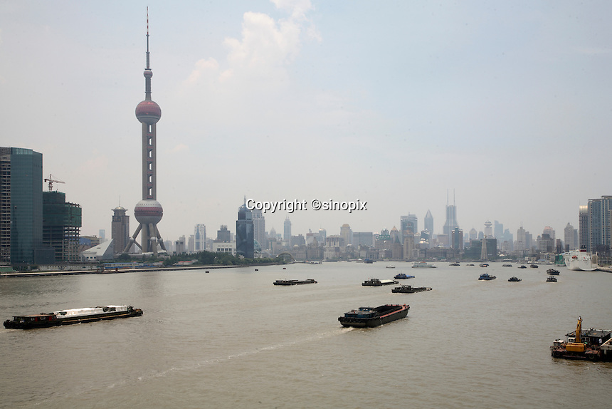 Barges travel on the Huangpu River past the Pudong Financial District in Shanghai, China..
