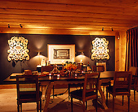 One wall of the dining room is covered in a deep brown fabric providing a backdrop for artwork and sculpture