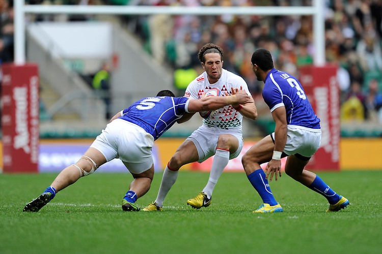 Mike Ellery of England is tackled by Alafoti Faosiliva (left) and Lio Lolo of Samoa during the iRB Marriott London Sevens at Twickenham on Saturday 11th May 2013 (Photo by Rob Munro)