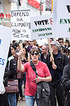 A protestor holds a sign and marches through downtown Toronto. Around 1500 people came out in Toronto today to take part in the Defend our Climate rally. The rally was a part of a national day of action drawing attention to pipelines, tar sands, climate change and other resource extraction that is exacerbating climate change, affecting First Nations and leading Canada towards a Petrostate.