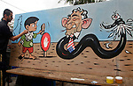 A Palestinian artist paints a mural depicting a child holding his shoe in the face of the US President George W. Bush (R), drawin in the shape of a satan, in the centre of Gaza City 09 January 2008, the day of Bush's arrival in Jerusalem at the start of a Mideast tour which includes stops in Israel and the Palestinian territories. Photo By: JINIPIX / Fady Adwan