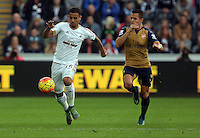 (L-R) Kyle Naughton of Swansea chased by Santi Cazorla of Arsenal during the Barclays Premier League match between Swansea City and Arsenal at the Liberty Stadium, Swansea on October 31st 2015