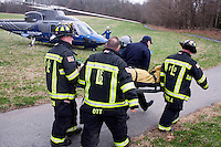 Firefighters carry a patient to a Boston MedFlight helicopter after the woman was injured in a one-vehicle car crash.  ..(no releases)