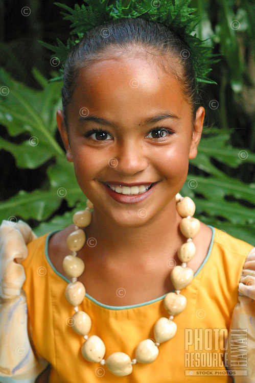 Polynesian girl wearing aloha wear with kukui nut lei. Smiling head and shoulders shot.