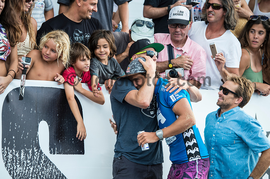 Pipeline, North Shore of Oahu, Hawaii Friday December 19 2014) Julian Wilson (AUS) is congratulated by Mick Fanning (AUS) and Lyndie Irons (HAW) after the scores were announced.- The final stop of the 2014  World Championship Tour, the Billabong Pipe Masters in Memory of Andy Irons, was  ccompleted today in NW double overhead surf. <br /> Gabriel Medina (BRA) became the first ever Brazilian World Champion after both rival contenders , Kelly Slater (USA) and Mick Fanning (AUS) were eliminated from the contest. Medina went onto finish 2nd overall behind Julian Wilson (AUS). <br /> In the overlapping heat format Wilson surf three consequent heats and still had enough entry to take out the 30 minute final.<br /> By winning the final Wilson also won the covered Vans Triple Crown of Surfing for best overall performance through the whole Triple Crown.<br /> <br /> The Billabong Pipe Masters in Memory of Andy Irons will determine this year&rsquo;s world surfing champion as well as those who qualify for the elite tour in 2015. As the third and final stop on the Vans Triple Crown of Surfing Series  the event will also determine the winner of the revered three-event leg.<br /> <br />  Photo: joliphotos.com