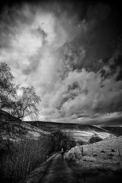 A lonely Hiker with back pack walks a tree lined old country road towards Jacobs Ladder in the Peak District with dark, brooding clouds overhead.