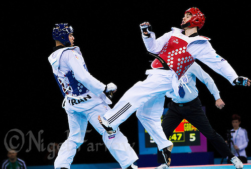 04 DEC 2011 - LONDON, GBR - Aaron Cook (GBR) (on right, in red) tries to strike Yousef Karami (IRI) (on left, in blue) during their men's -80kg category quarter final round contest at the London International Taekwondo Invitational and 2012 Olympic Games test event at the ExCel Exhibition Centre in London, Great Britain .(PHOTO (C) NIGEL FARROW)