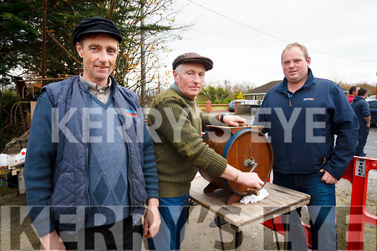 Paddy Ashe and David Savage give Moss Trant a helping hand in churning butter at the Steam Threshing Machine exhibition in Ballymac on Sunday last in aid of Kerry Hospice and the Alzheimers Society.