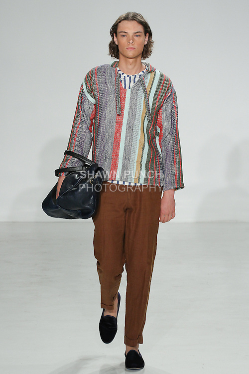 Model walks runway in a technicolor drug rug, and rust linen Hollywood trouser from the Palmiers du Mal Spring Summer 2017 collection by Brandon Capps and Shane Fonner, with Moore & Giles navy taylor duffle, at Skylight Clarkson Square on July 14 2016, during New York Fashion Week Men's Spring Summer 2017.