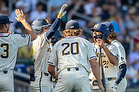 Michigan Wolverines outfielder Jordan Brewer (22) celebrates with his teammates after scoring against the Vanderbilt Commodores during Game 1 of the NCAA College World Series Finals on June 24, 2019 at TD Ameritrade Park in Omaha, Nebraska. Michigan defeated Vanderbilt 7-4. (Andrew Woolley/Four Seam Images)