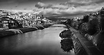 Kamo River, Kamo-gawa, with pathways along the banks and people fishing. Kyoto beautiful panoramic sunrise scenery from Shijoo bridge with Sanjo bridge in the background in dramatic autumn morning light. Kyoto, Japan 2017. Black and white.