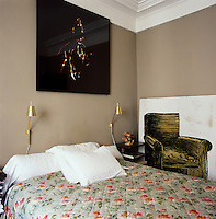 The bedroom is simply furnished with an old fashioned floral cover and a pair of gilded wall lamps